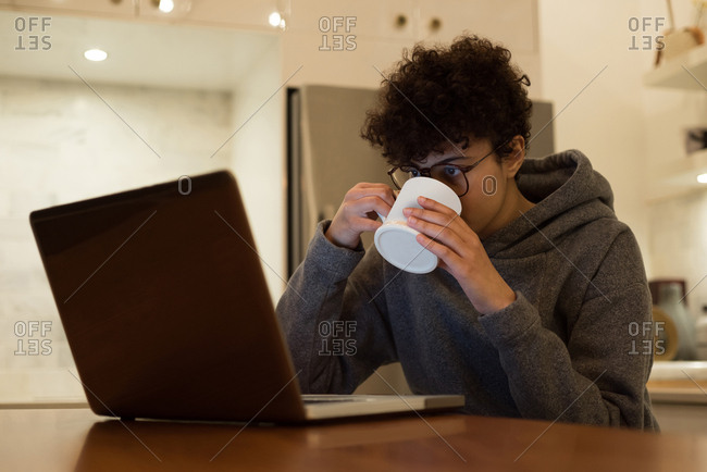 Beautiful woman using laptop while having coffee in kitchen