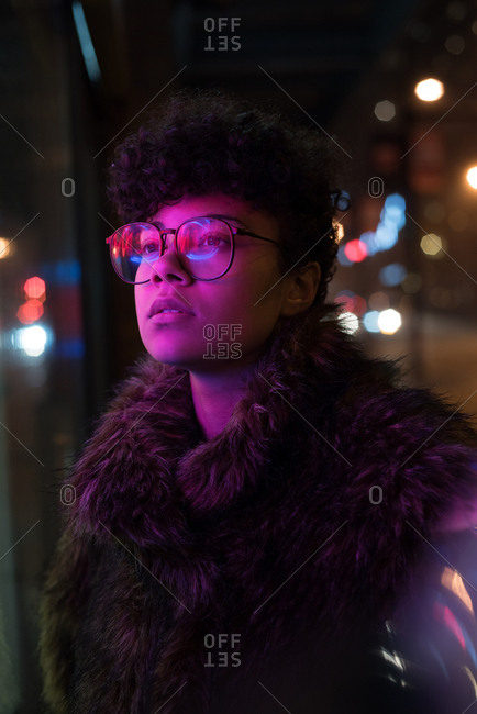 Thoughtful woman standing on street at night