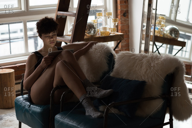 Beautiful woman using digital tablet while relaxing on chair n living room