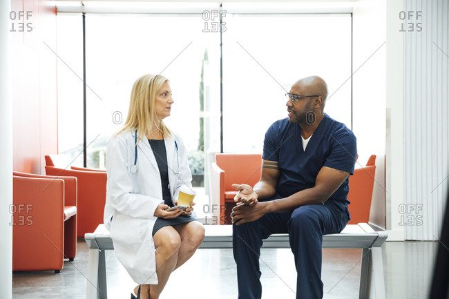 Mature doctor and nurse discussing while sitting on bench in hospital