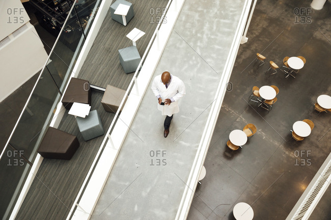 High angle view of mature male doctor using mobile phone while walking on walkway in hospital