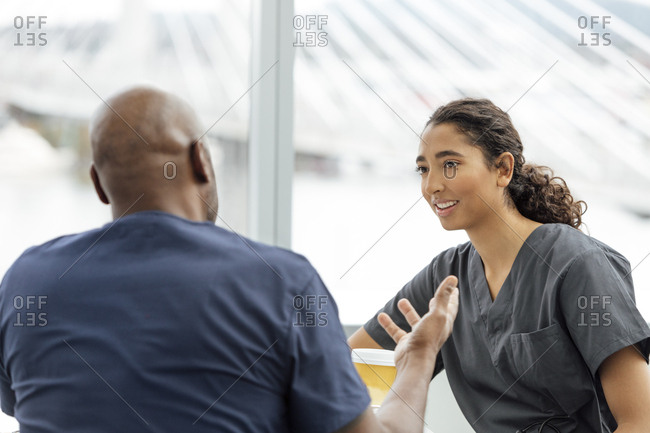 Mature male nurse talking with female colleague in hospital