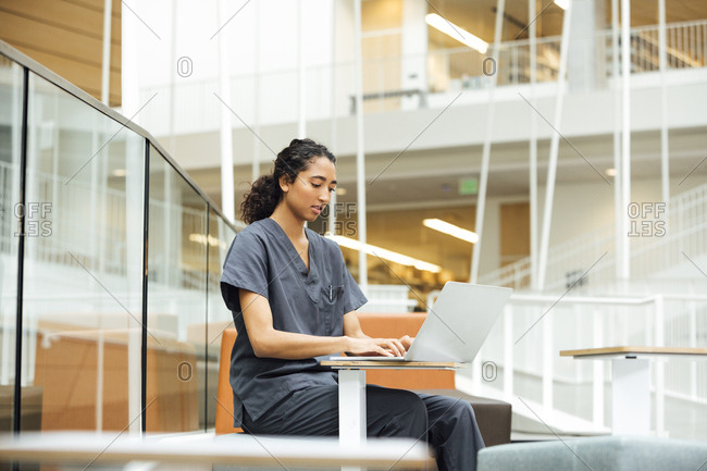 Young nurse using laptop in hospital