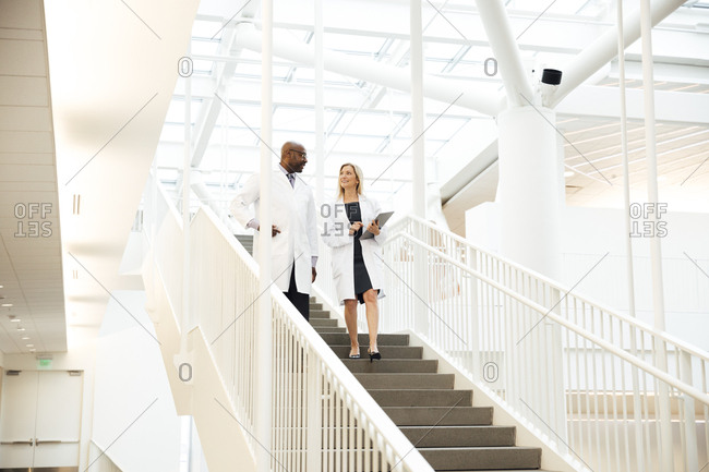Mature male and female doctors discussing while walking down stairs in hospital