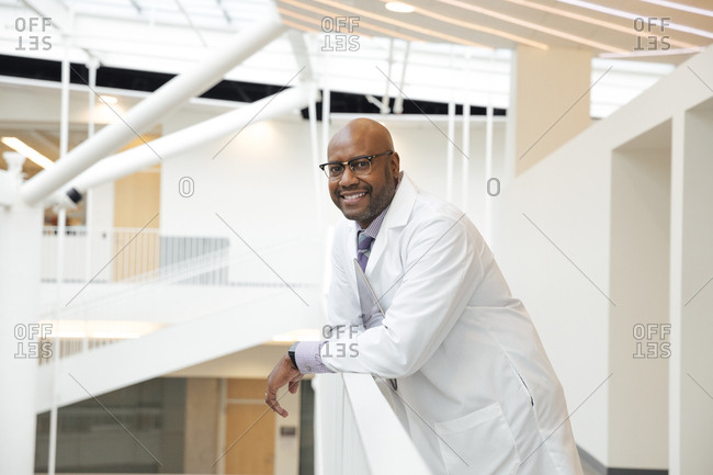 Portrait of smiling mature male doctor leaning on railing in hospital