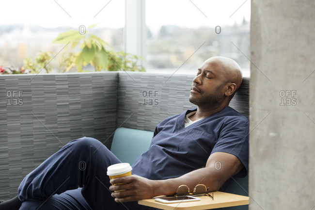 Mature male surgeon holding coffee cup while resting on sofa in hospital
