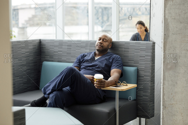 Mature male doctor holding coffee cup while resting on sofa in hospital