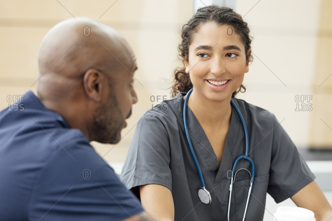 Smiling young nurse talking with male colleague in hospital