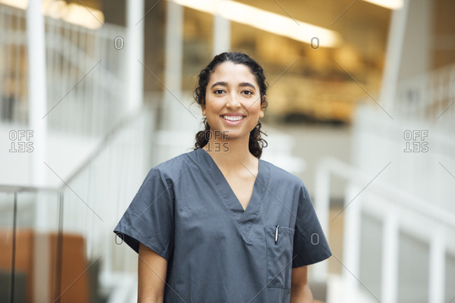 Portrait of smiling young nurse wearing scrubs standing in hospital