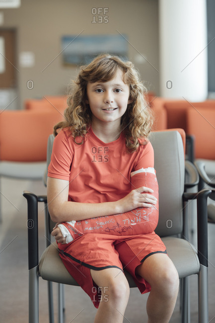 Portrait of girl with plastered arm sitting on chair in hospital