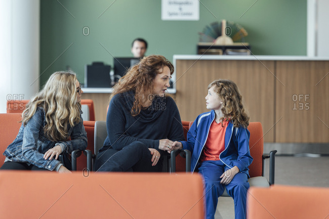Mother talking with daughter in waiting room at hospital