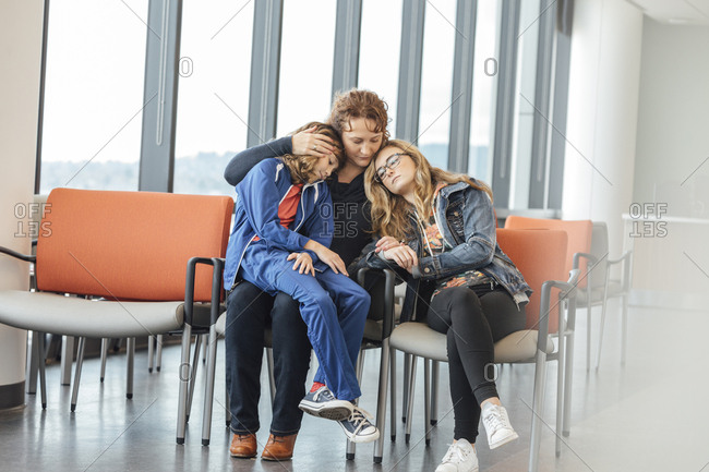Sad mature woman and her daughters in waiting room at hospital