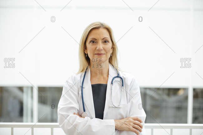 Portrait of mature female doctor standing arms crossed in hospital