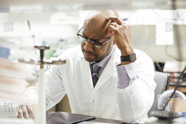 Thoughtful male medical researcher using digital tablet in laboratory at hospital