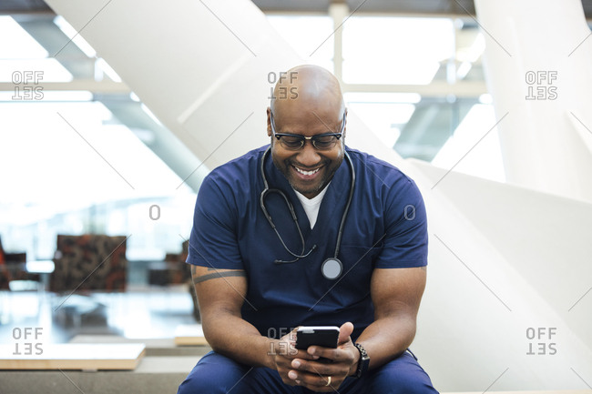 Smiling mature male surgeon using mobile phone in hospital