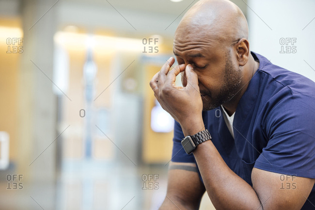 Tired male surgeon pinching his nose bridge in hospital