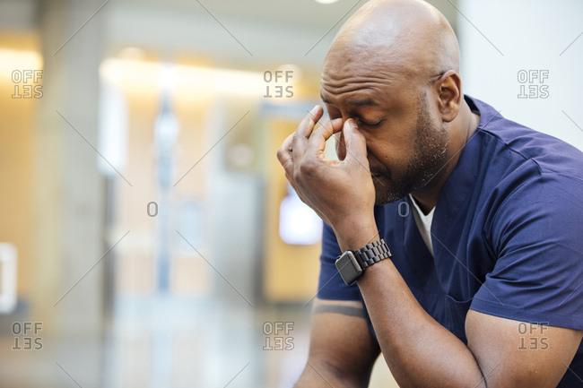 Tired male surgeon pinching his nose bridge in hospital