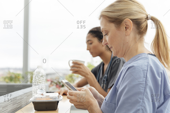 Side view of mature surgeon using mobile phone during break at hospital