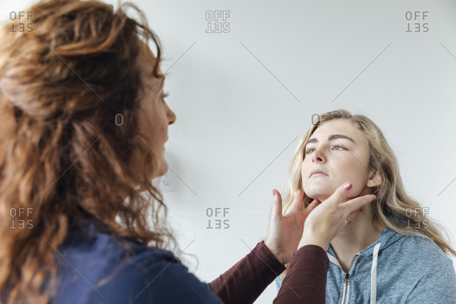 Mature female doctor examining glands in the neck of teenage girl at hospital