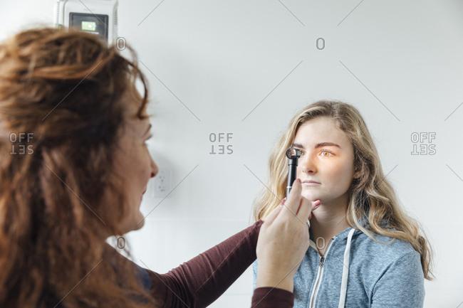 Female doctor examining teenage f