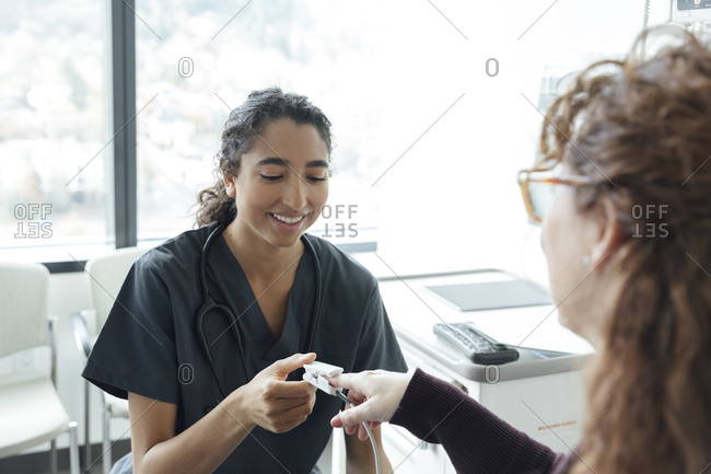 Smiling young nurse adjusting oximeter on woman's finger in hospital