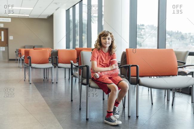 Full length portrait of girl with plastered arm sitting on chair in hospital