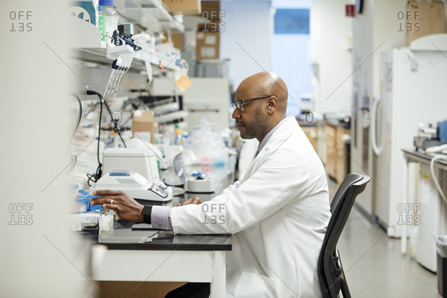 Side view of mature male medical researcher working in laboratory at hospital