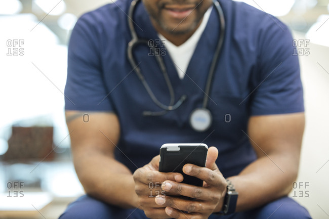 Midsection of mature male nurse using mobile phone in hospital