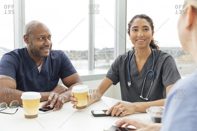 Young female nurse  talking with colleague in break room at hospital