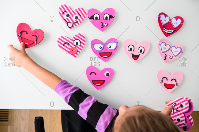 Young girl positioning Valentine heart she just made