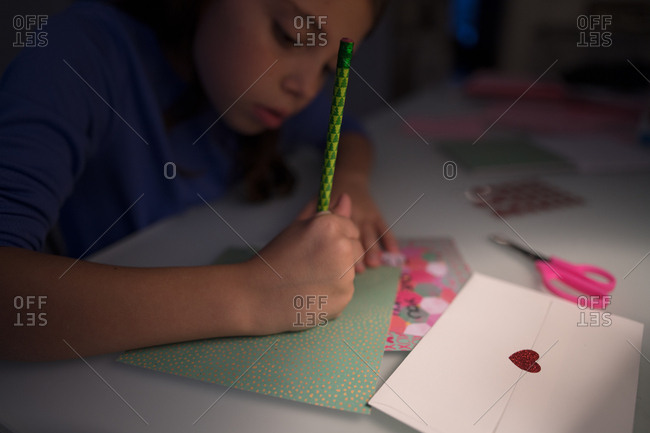 Young girl writing Valentine's letters by the light of desk lamp