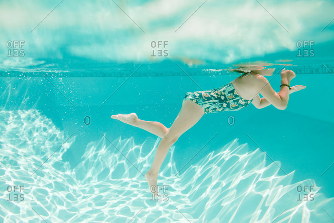 Young girl swims in a pool