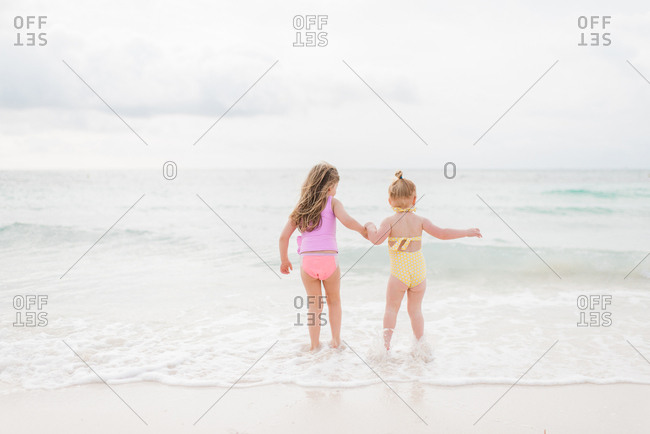 Little girls play in the surf