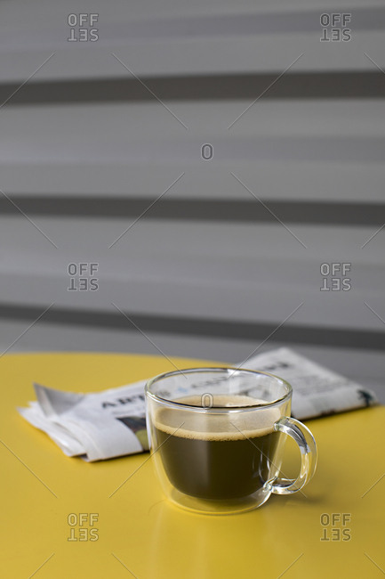Cup of fresh coffee on bright cafe table