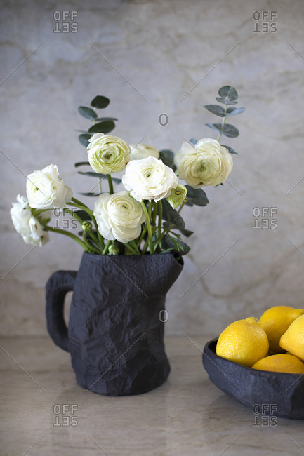 Still-life flowers and lemons in handmade stoneware