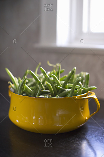 Bowl of green beans on wooden table