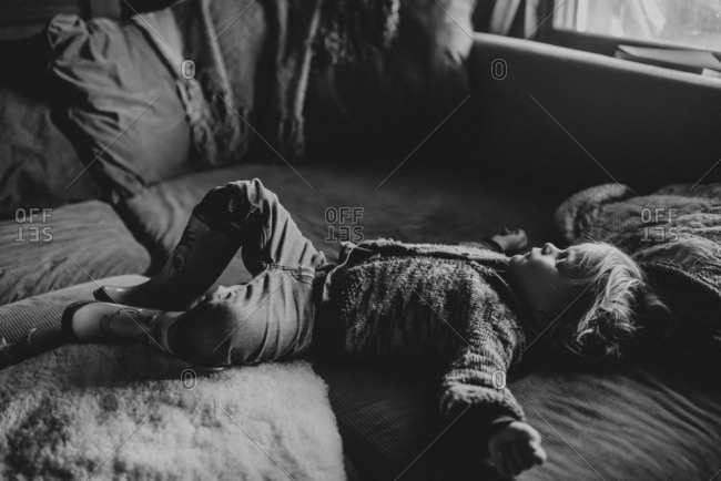 Young boy sleeping spread eagled and fully dressed on the couch