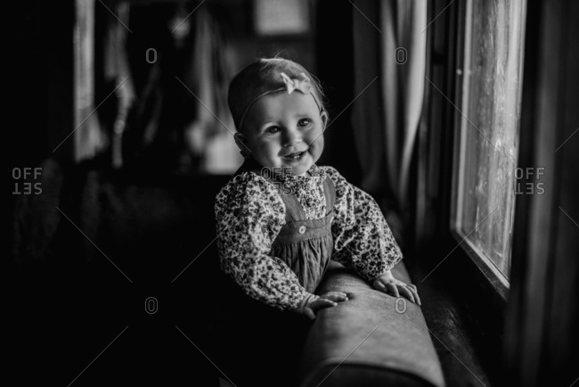 Little girl standing on couch and smiling happily