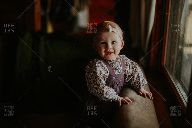 Portrait of happy little girl standing on couch