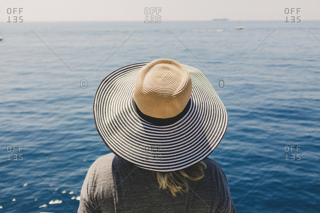Traveling woman in hat looking at wide ocean view