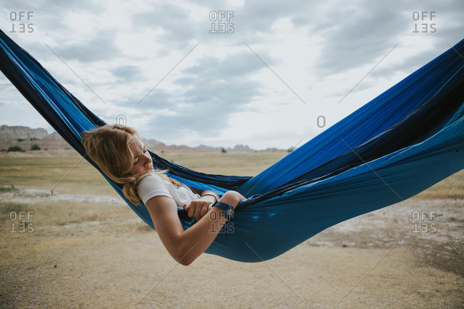 Teen girl lounging in a blue hammock outside