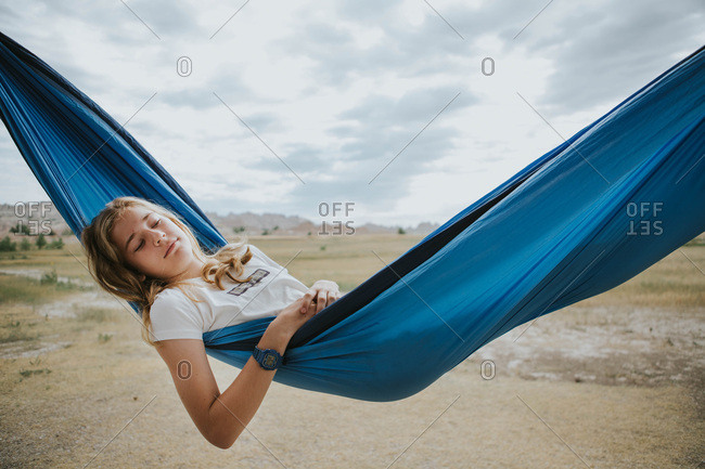 Teen girl resting in a blue hammock outside