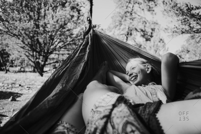 Black and white image of a laughing girl in a hammock