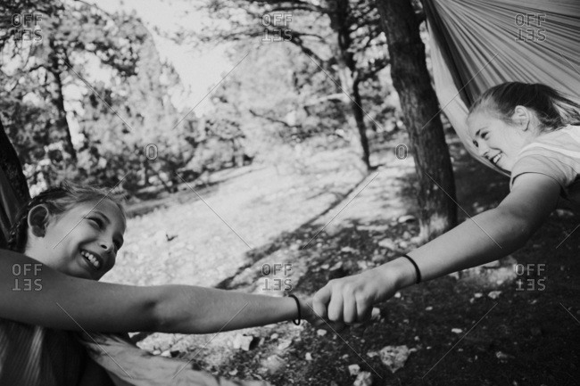 Black and white image of a two girls holding hands in a hammock