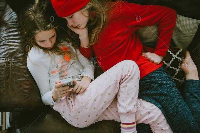 Girls cuddling on the couch playing on a mobile device