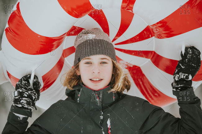 Girl playing in the snow with striped inner tube
