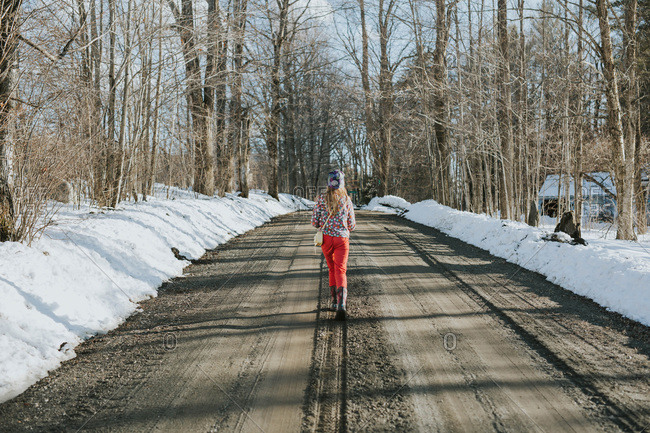 Young girl walking down a dirt road in winter