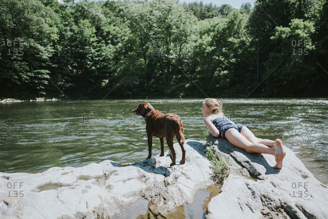 Little girl and a chocolate lab puppy at the river