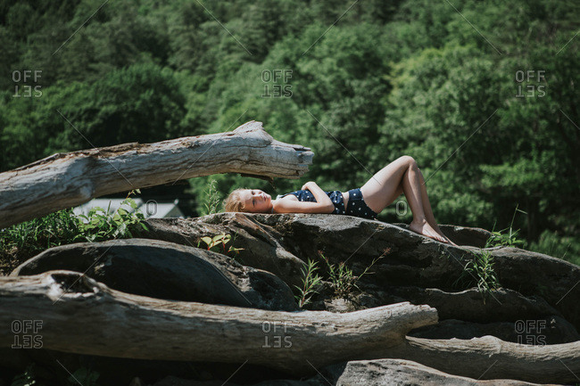 Little girl lying on rock sunbathing