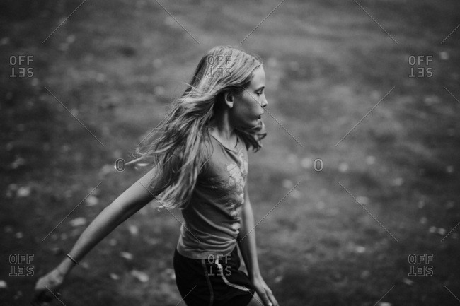 Black and white image of a young girl with long blonde hair spinning